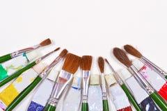 Pinceaux et tubes de couleur utilisés d'isolement sur un fond Photographie stock