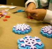Pincel pequeno verde com stampers do floco de neve e mãos dos childs imagem de stock royalty free
