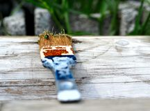 Pincel usado que se encontra na prancha de madeira branca friccionada Foto de Stock Royalty Free