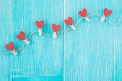 Pinces à linge avec des coeurs sur le fond en bois de corde approximative et de vintage bleu Concept de l'amour Photos libres de droits
