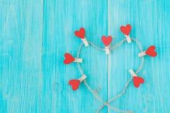 Pinces à linge avec des coeurs sur le fond en bois de corde approximative et de vintage bleu Concept de l'amour Photo libre de droits