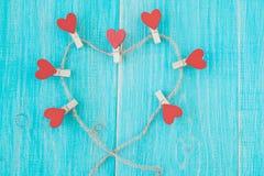 Pinces à linge avec des coeurs sur le fond en bois de corde approximative et de vintage bleu Concept de l'amour Photographie stock