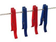 Pinces à linge bleues et rouges sur une corde à linge (+ chemin de découpage) Photographie stock libre de droits