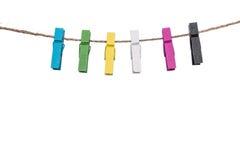 Pinces à linge colorées sur une corde à linge, les travaux domestiques de cheville de bride Photos stock