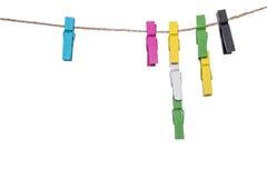 Pinces à linge colorées sur une corde à linge, les travaux domestiques de cheville de lien de bride Photo libre de droits