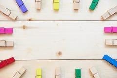 Pinces à linge en bois colorées sur le fond en bois Images stock