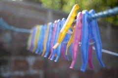 Pinces à linge en plastique s'étendant sur le fil photo stock