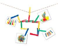 Pinces à linge et photos colorées sur une chaîne de caractères Photographie stock libre de droits