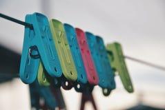 Pinces à linge multicolores sur la corde à linge Images stock