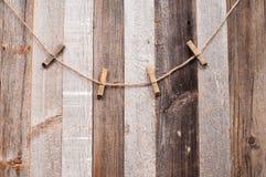 Pinces à linge sur la corde sur un fond en bois Photo libre de droits