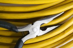 Pinces électriques avec le câble jaune images stock