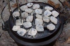 Pinces ajustant des briquettes sur un couvercle de four néerlandais Image stock