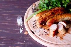 Pinces de barbecue avec le sausege Photographie stock