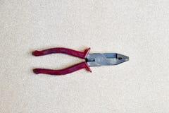 Pinces manipulées rouges sur le fond en bois Photographie stock