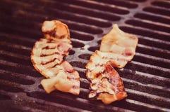Pinces tenant la tranche grillée fumée croustillante de lard de barbecue, photos libres de droits
