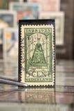 Pinceta trzyma znaczek pocztowego drukuje holandiami na temat głowach państwych, Pokazuje królowej Wilhelmina obraz stock