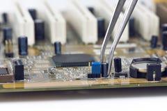Pincetholding en het Assembleren Elektrolytische Condensatoren en Leiders Royalty-vrije Stock Afbeeldingen