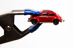 Pinch of gas prices. A red car feeling the pinch of high gas prices Royalty Free Stock Photo