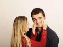 Pinching cheeks. Blond girl pinching guy's cheeks royalty free stock photo