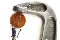 Pinching a Penny in a C Clamp. Isolated on White Royalty Free Stock Photography