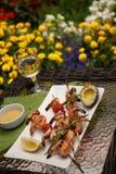 Pinchos asados a la parrilla de los camarones para la cena en jardín Fotografía de archivo