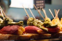 Pinchos con pimienta verde y el jamón en rebanadas de pan fotografía de archivo