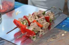 2 pinchos de los kebabs con la pimienta roja y el perejil en saucekebabs antes de freír Foto de archivo