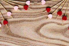 Pinchos de madera rojos y rosados para la comida con un corazón Fondo de madera para el día del ` s de la tarjeta del día de San  fotografía de archivo libre de regalías