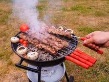 Pinchos de torneado de un cocinero de la carne en una barbacoa Fotografía de archivo