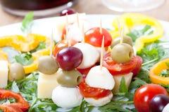 Pinchos del queso con la mozzarella, los tomates de cereza, las aceitunas y la pimienta dulce Imagen de archivo