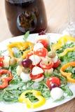 Pinchos del queso para el arrancador, con la mozzarella, los tomates, la pimienta dulce y las aceitunas, en la ensalada de cohete Fotografía de archivo libre de regalías