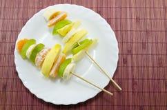 Pinchos deliciosos de la fruta en una placa blanca Imagenes de archivo