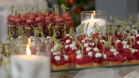 Pinchos med rödbeta på en exponeringsglasställning med brinnande stearinljus stock video