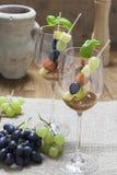 Pinchos y uvas del queso en una copa de vino Imagen de archivo libre de regalías