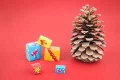 Pincone和五颜六色的圣诞节礼物盒 库存图片