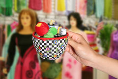 Pincushion. Woman holding pincushion with dresses in the background Royalty Free Stock Images