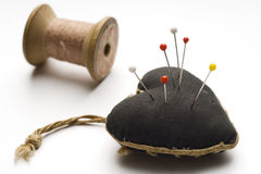 Pincushion. A pincushion and a spool of thread on white Stock Images