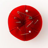 Pincushion. Red pincushion with pins and needles Stock Image
