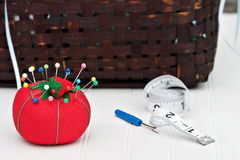 Pincushion. Red pincushion with sewing basket in the background. Shallow DOF Stock Photo
