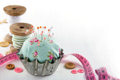 Pincushion in an antique  metal cupcake. Green handmade floral pincushion in an old metal cupcake with buttons and spools of thread and lace, sewing concept Stock Photography