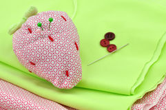 Pincushion and Buttons. Pins and buttons and a strawberry pincushion Stock Image