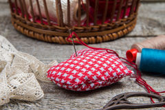Pincushion heart close up on a background basket with needlework Handmade Stock Photos