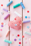 Pincushion in a heart shape. And colorful yarns on pink Stock Photography
