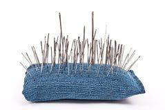 Pincushion with lot of needles. On white Stock Photo