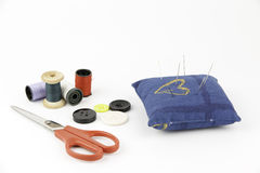 Pincushion with needles, buttons, scissors and threads Royalty Free Stock Images