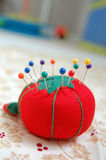Pincushion with Pins. A strawberry pincushion with multi colored pins in it Stock Photos