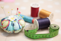 Sewing accessories. Pincushion, pins, tape and spools, closeup with  blurry background Royalty Free Stock Photos