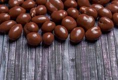 Pinda's in chocolade Zoete pinda op de achtergrond Houten achtergrond Zoete pinda's in chocolade voor thee en koffie Stock Afbeelding