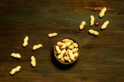 Pinda's in natuurlijke kokosnotenkom op houten achtergrond Het vegetarische voedsel, producten voor juiste voeding, sluit omhoog, stock afbeelding