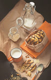 Pindakoekjes, kop van melk, glaskruiken op verfrommeld document Stock Foto's